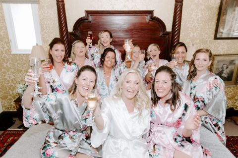 Group shot of a cheering bridal party sat on a four poster bed holding prosecco