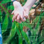 Couple holding hands against street art in Shoreditch