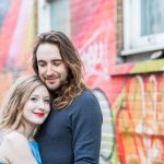 Natural photo of couple smiling at camera against street art graffiti