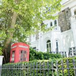 Traditional red british telephone box in a garden in London
