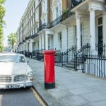 A classic white Volvo parked next to a traditional red postbox in West london