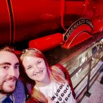 Couple posing in front of Hogwarts Express train