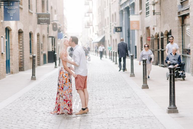 Summery couple kissing in cobbled sunlit street