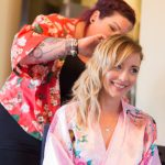 Bridesmaid in silk robe having her hair done ready for wedding