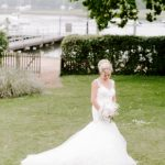 Beautiful bride looking at her bouquet with Marina behind