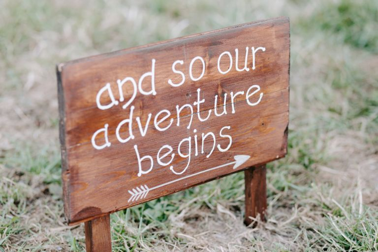 'Our adventure begins' here wedding day sign