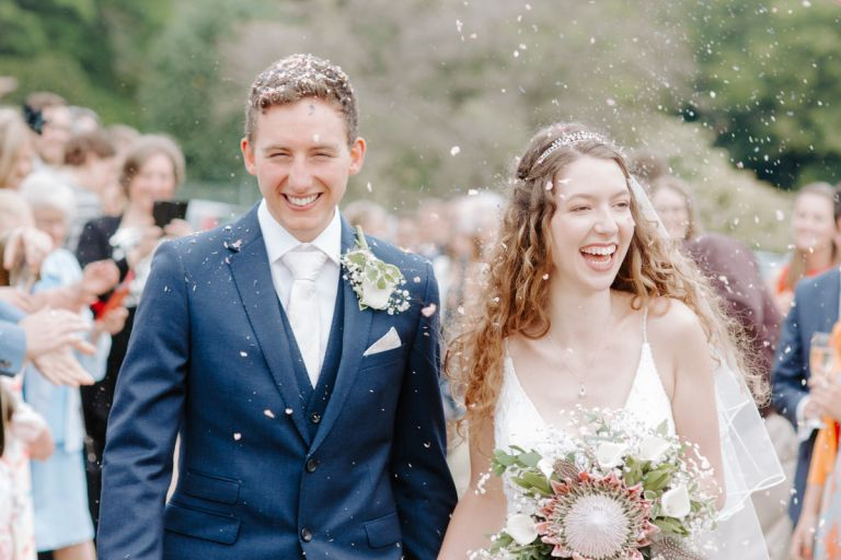 Bride and groom getting showered with confetti