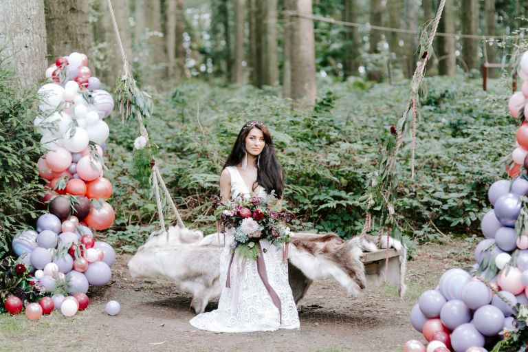 A bohemian bride sat on an outdoor swing with balloons