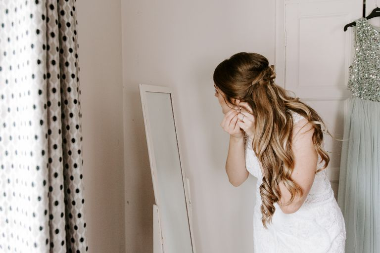 Bride putting her earrings in before wedding
