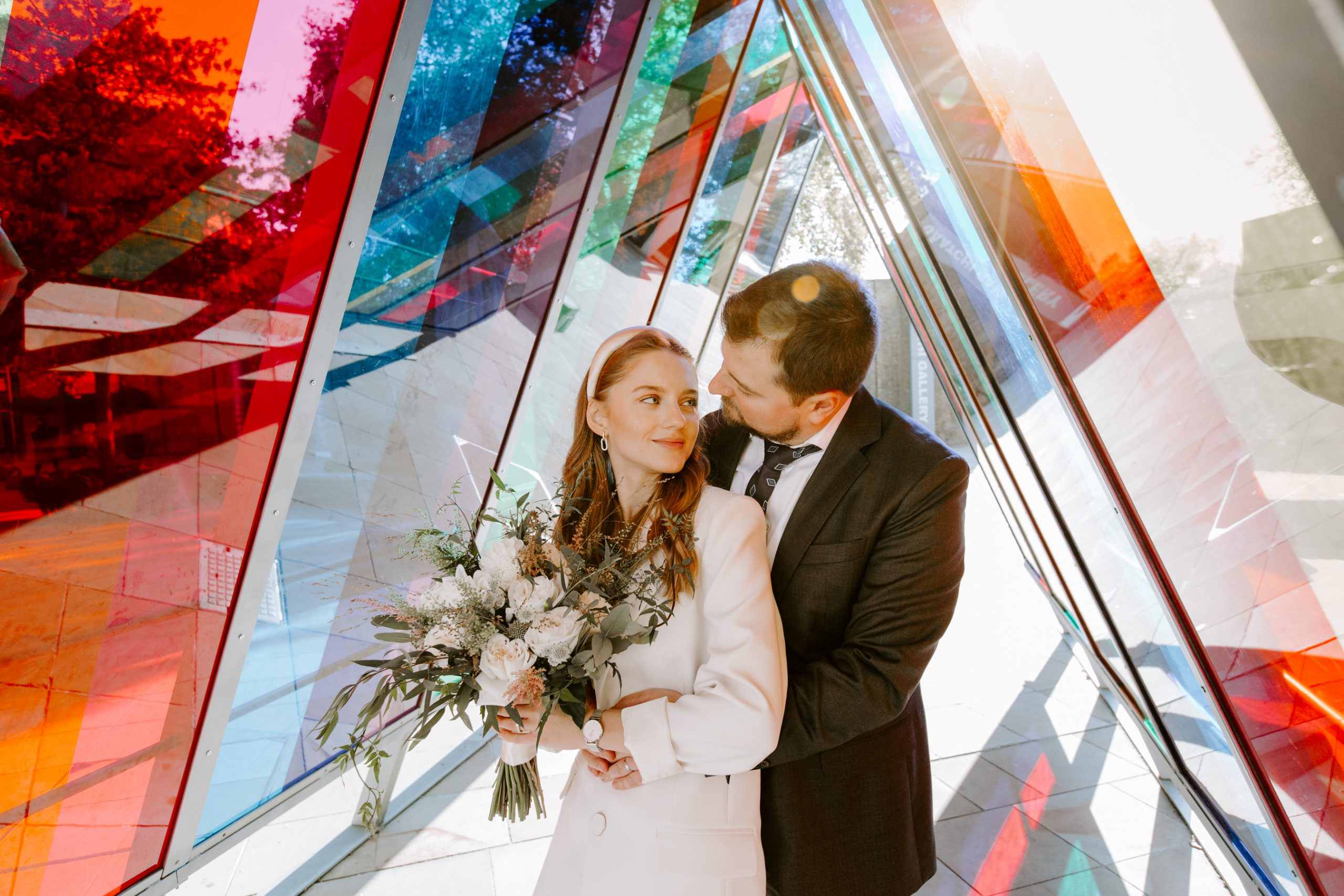Bride and groom smiling in a coloured light tunnel