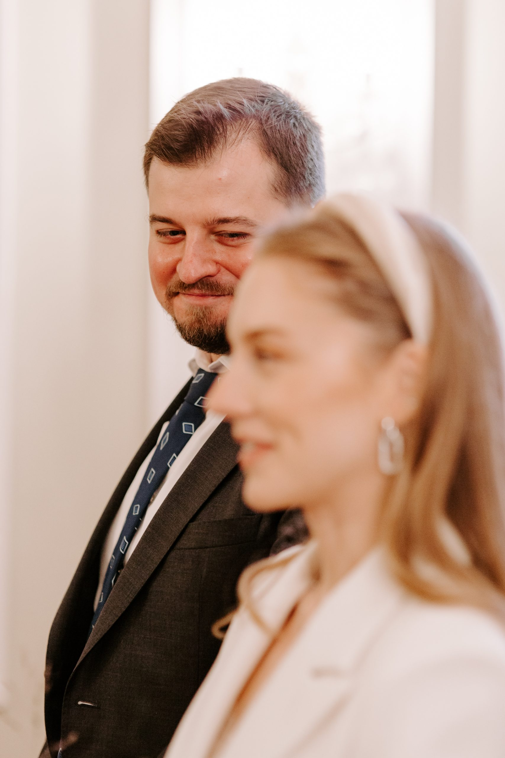 Groom smiling at bride as she says her vows in London
