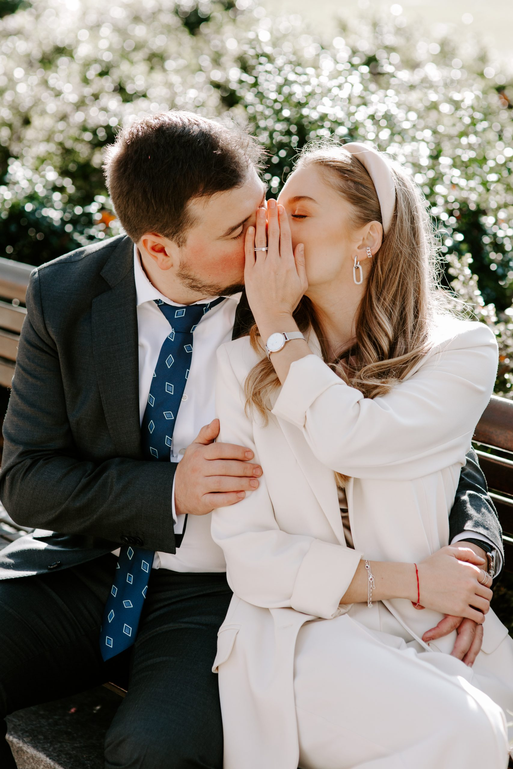 Bride and Groom kissing and hiding their face with hand to show wedding ring