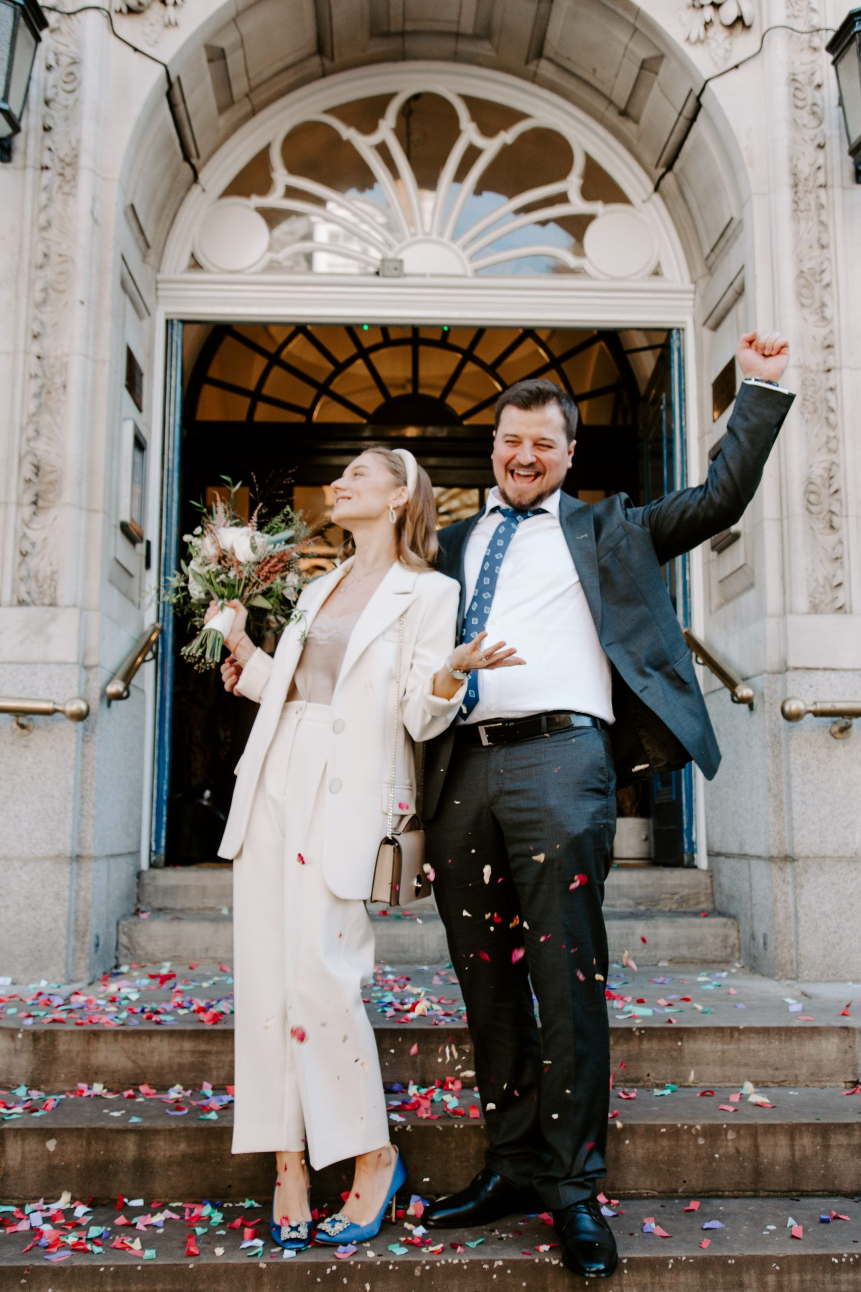 Bride and groom cheering on steps of Chelsea Town Hall