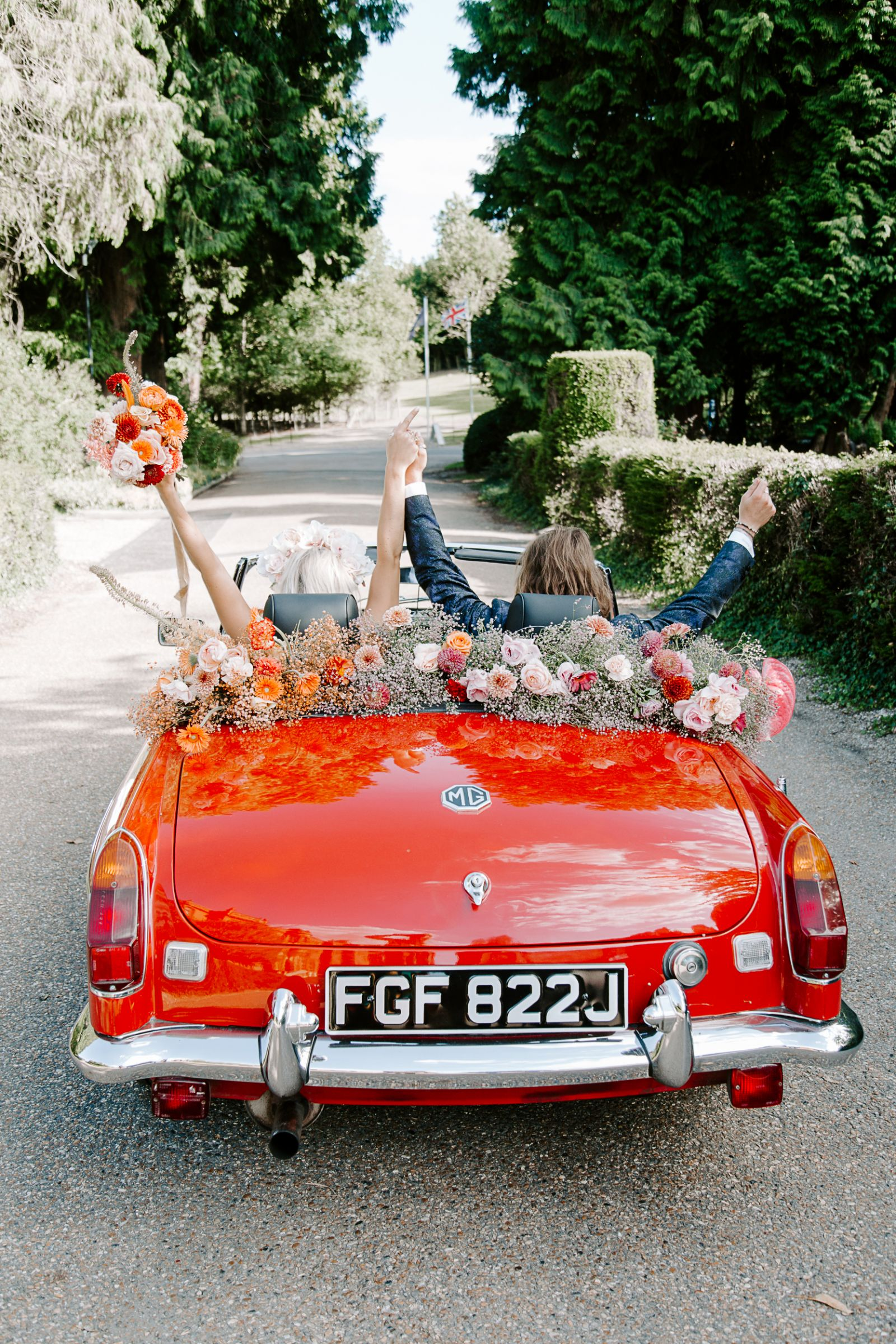Bride and groom in MG wedding car at Woldingham School