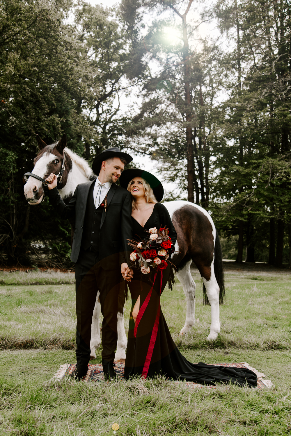 Bride and groom wearing black with horse